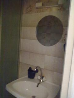 Coin salle de bain, avec miroir. Sur la gauche : douche et lave-linge