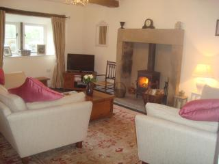 spacious lounge with cosy log burner and comfy sofas to sink into after a long walk