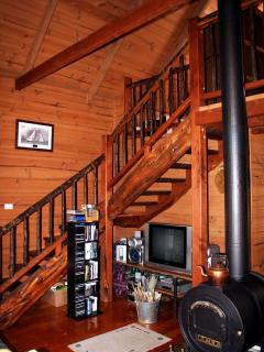 'Tassie Barrel' wood heater, entertainment area and rustic, timber staircase.