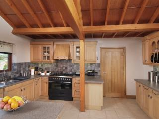 Fully integrated oak kitchen with fridge, freezer, dishwasher, wine cooler and range cooker.