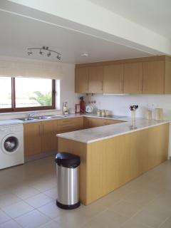 Modern fully fitted kitchen with fridge freezer, oven, microwave, washing machine and dishwasher.