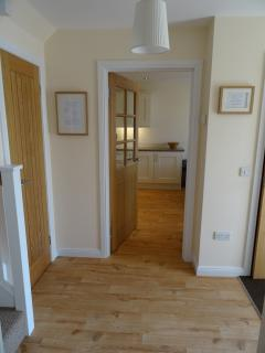 Downstairs hall leading to large cupboard under the stairs and a downstairs cloak room
