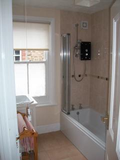 New bathroom with low level bath and Mira electric shower
