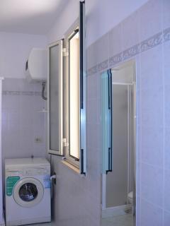 bagno con doccia, scaldabagno e lavatrice