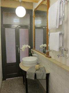 A large, antique gold-leaf mirror and mahogany wooden demi-lune vanity blend with modern fixtures.