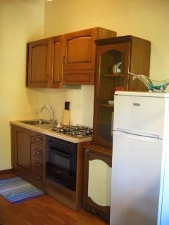l'angolo cottura dotato di forno, frigo e tutto il necessario per preparare e gustare pasti in casa