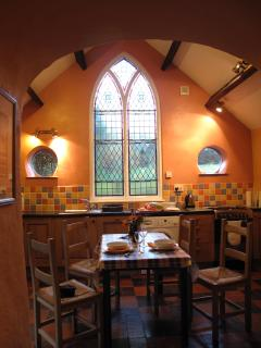 A moody ex chapel window in the kitchen with views over a wild flower meadow