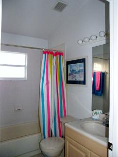 Guest bathroom with bath and overhead shower situated between the 2 twin bedrooms