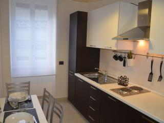 cucina con tavolo allungabile, stoviglie e suppellettili, frigorifero, forno a microonde e Nescafè.