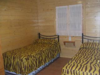 Habitación con dos camas una de ellas convertible en litera. Vistas al huerto del camping y acampada