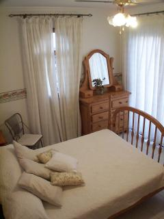 Double bedroom with patio doors onto terrace with views to sea and mountains.