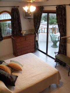 King size comfortable bed in large bedroom with views to sea and mountain