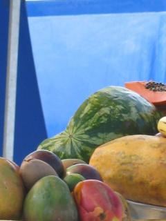 Vendors offer tropical fruits, 'café con leche' from colorful flasks, and piping hot fritt
