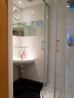 Bathroom with walk in shower, black floor tiling and porthole features.