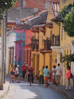 Colorful buildings line cobblestone streets faded after centuries in the sun