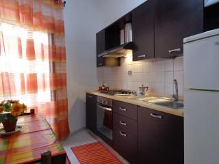 Cucina abitabile dotata di tavolo da pranzo e ampio balcone.