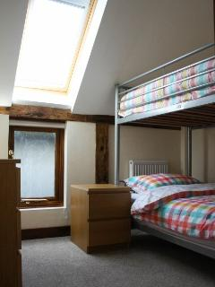 Twin room with adult size bunk beds , 2 chest of drawers, reading light & shelf & velux roof