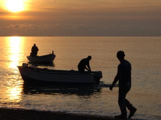 Bringing in the boats at sunset on the adjoining beach.