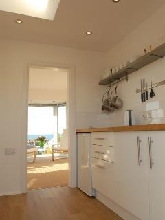 View from entrance through kitchen to living room and sea beyond