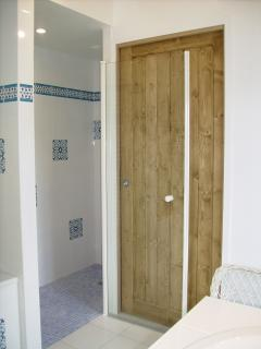 A spacious Italian shower with a large bath to its left