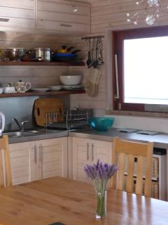 Kitchen area with window opening through to deck