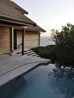 Pool deck with view of ocean in background