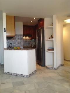 Kitchen with fridge freezer, microwave, oven hob,  kettle, cutlery, crockery, pans and utensils