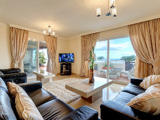 Lounge and TV area with viol curtains open and great sea views.