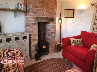 The cosy sitting room has a fireplace with woodburning stove