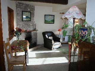 Stable Cottage's sitting/dining room has an open log fire