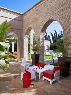 Le patio avec son petit salon bas rouge et blanc.