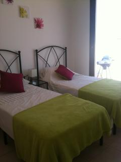 2 single beds fitted wardrobe and dressing table, bedroom leads onto the balcony