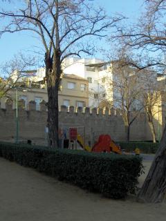 Parque infantil dentro de los Jardines del Valle con muralla original de la ciudad al fondo