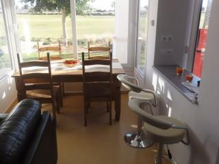 Lounge area with 2 bar stools and dining table and chairs