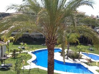 View overlooking large pool from balcony, and  small childrens pool, with sun beds and umbrellas.