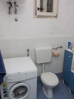 The bathroom with a toilet and a washing machine