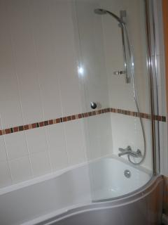 The bathroom with large bath and good shower over, sink and toilet.