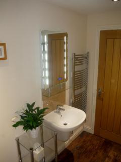 Large bathroom with illuminated mirror and heated towel rail