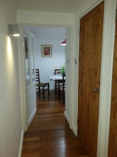 Downstairs corridor, leading to kitchen. Wooden doors to second w.c and hand basin, walk in storage.