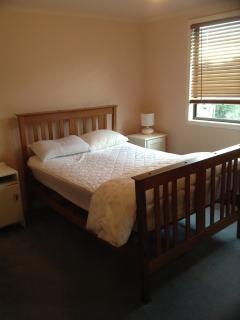 Double bed, dressing table and a wardrobe in main bedroom