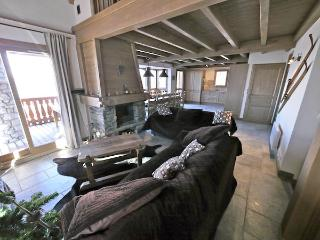 Open plan living area with log fire and large balcony leading off