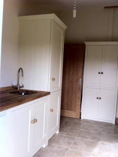 Utility room with washing machine, sink and freezer