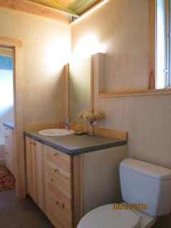 Bathroom with concrete counters and natural light.