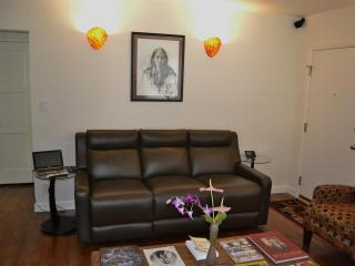 Very comfy reclining leather couch, ASUS computer, coffee table, sconces on, Bose surround speaker