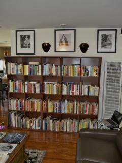 Bookcase in living room with sconces on, wall heater on right