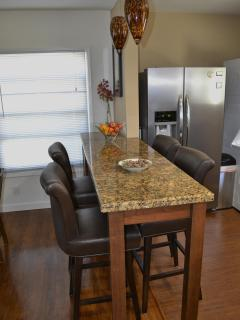 Granite bar between dining area & kitchen, comfy leather swivel bar stools, pendants off