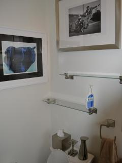 Glass shelves for toiletries in bathroom above toilet