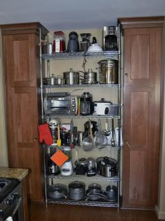 Cleaning cabinet on left, pantry on right,Metro kitchen rack with pots, pans & small appliances