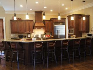 main level kitchen with many bar stools and high-end appliances