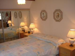 Spacious master bedroom, comfortably furnished with dual aspect windows.